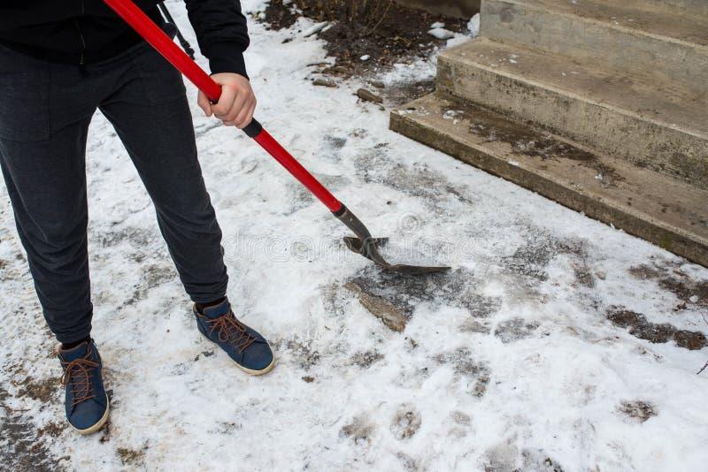Rupture de travailleur, nettoyant la glace avec une pelle images libres de droits