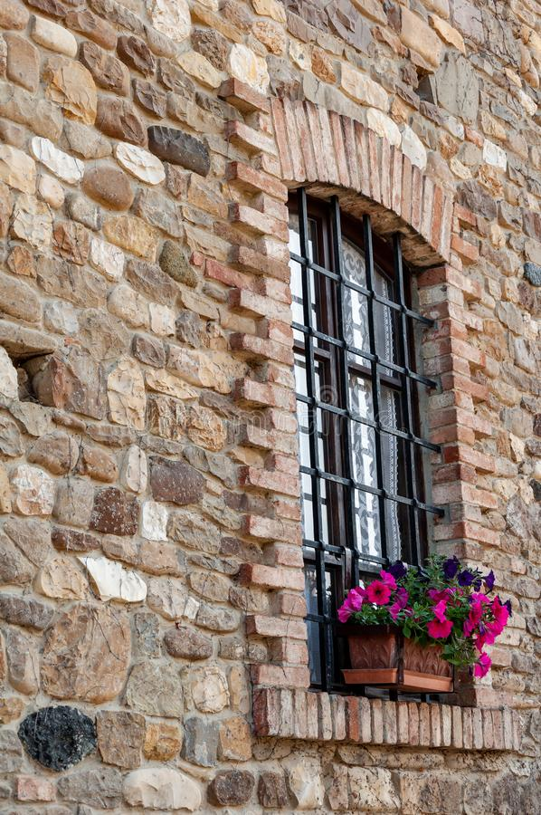 Arched window with iron grate, on ancient wall of stones and bricks. Rural ancient house in the Po valley, Italy. Window with flower pot inserted into the wall stock image