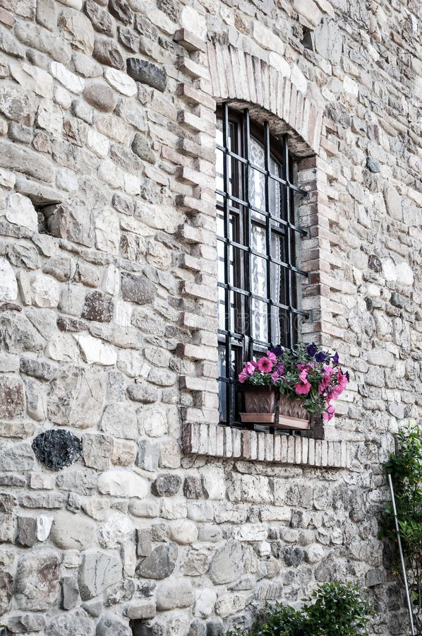 Arched window with iron grate, on ancient wall of stones and bricks. Rural ancient house in the Po valley, Italy. Window with flower pot inserted into the wall stock photography