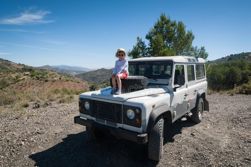 Rural Andalucia. Spain. 06/10/2016. Little girl admiring views while sitting on front spare tyre on a bonnet hood in 4x4 terrain v stock photo