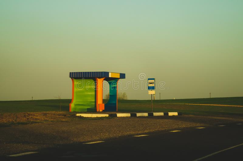 Rural bus stop on the country road with the field stock images
