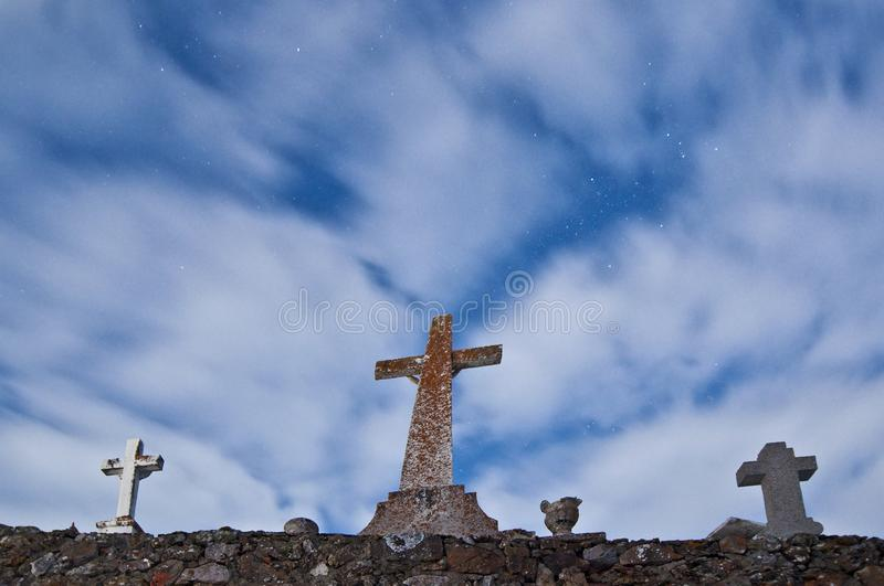 Christian crosses at cemetery under cloudy moonlight night sky royalty free stock image