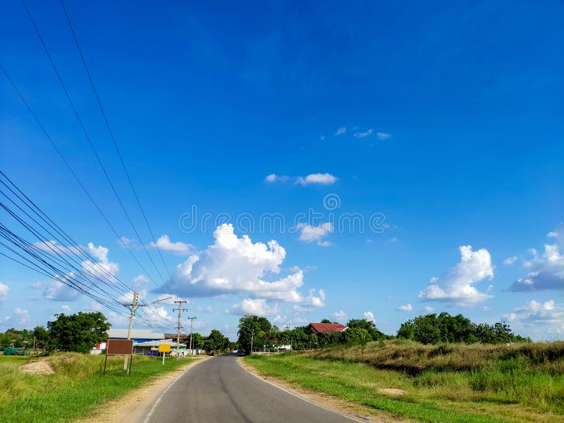 Rural country roads, one road in Thailand, without cars, background, blue sky and clouds on clear days stock photo