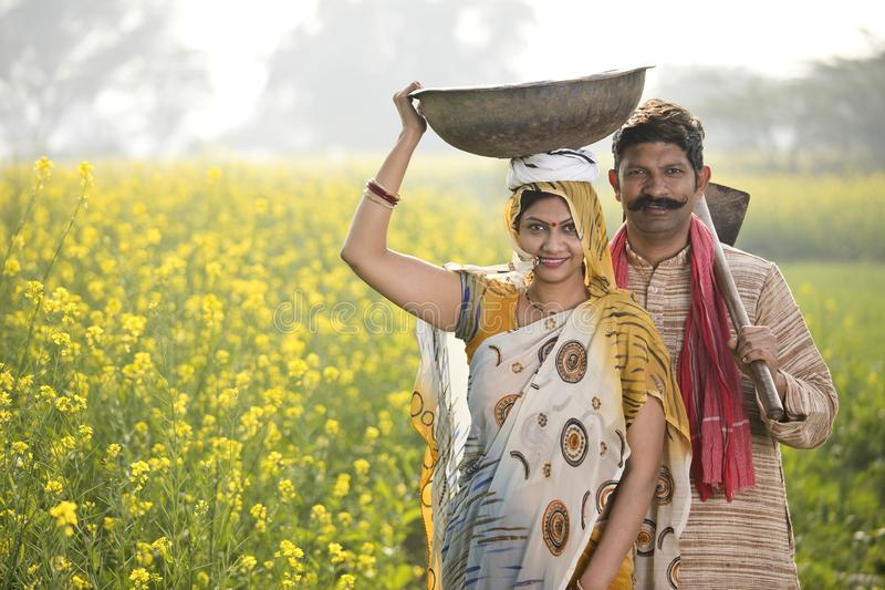 Rural couple with iron pan and hoe in agricultural field. Rural Indian couple with iron pan and hoe in rapeseed agricultural field stock photography
