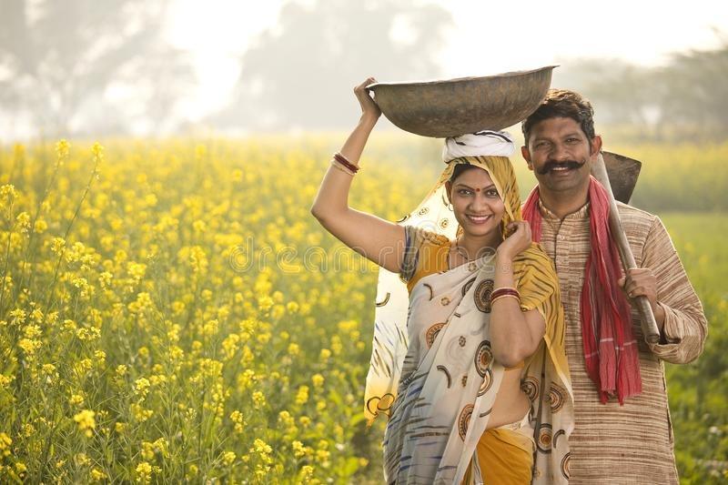 Rural couple with iron pan and hoe in agricultural field. Rural Indian couple with iron pan and hoe in rapeseed agricultural field royalty free stock images