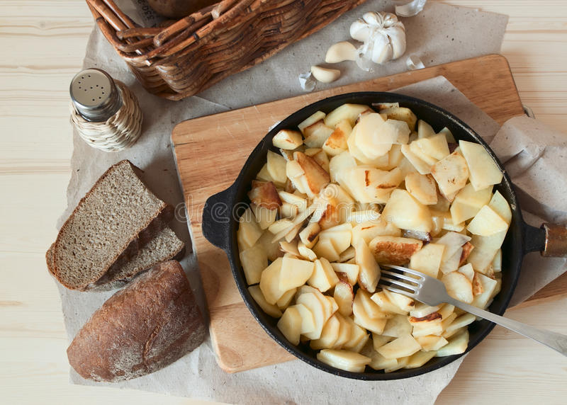 Rural dinner. Rural fried potato on a frying pan, fork and garlic on a chopping board royalty free stock images