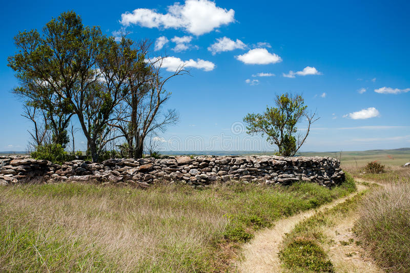 Rural dirt road. With blu sky and rocky wall royalty free stock photos