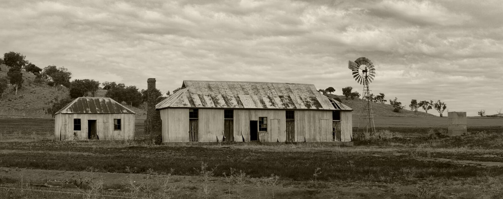Rural farmlands windmill and outbuildings. Rural farmlands with rusty corrugated tin outbulldings sheds and windmill now in disrepair stock image