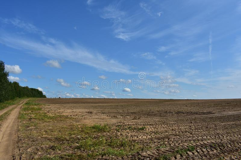 Rural field road along the woods and landscaped land of fresh arable land the Mick stay here and play, the sky clouds horizon stock photo