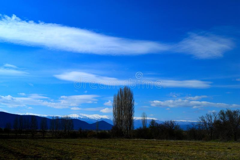 Rural fields. Green fields and beautiful white clouds in Prespes region, Greece royalty free stock image