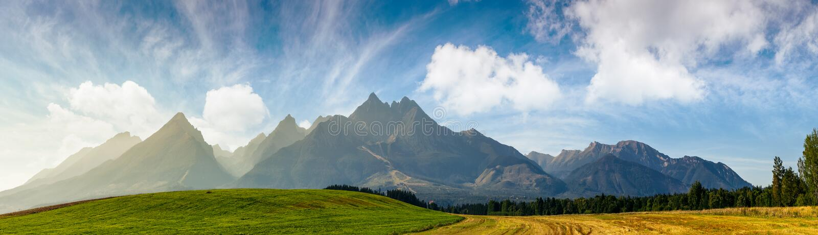 Rural fields near Tatra Mountains in summer time. Beautiful panorama of agricultural area. gorgeous mountain ridge with high rocky peaks stock photos