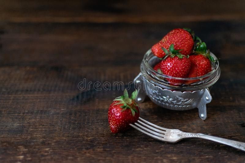 Rural fresh organic strawberry in metal bowl and fork on dark wooden rustic table. Red raw strawberry on a dark wood background. stock photography