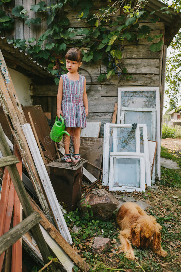 Rural girl with her dog among the old wooden trash royalty free stock photo