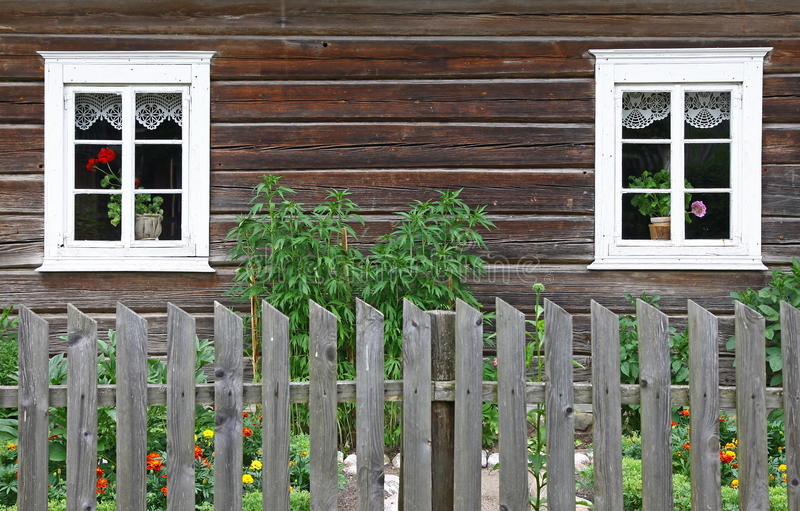 Rural house with two windows. Picture of an old rural house with two windows and the wooden fence royalty free stock image
