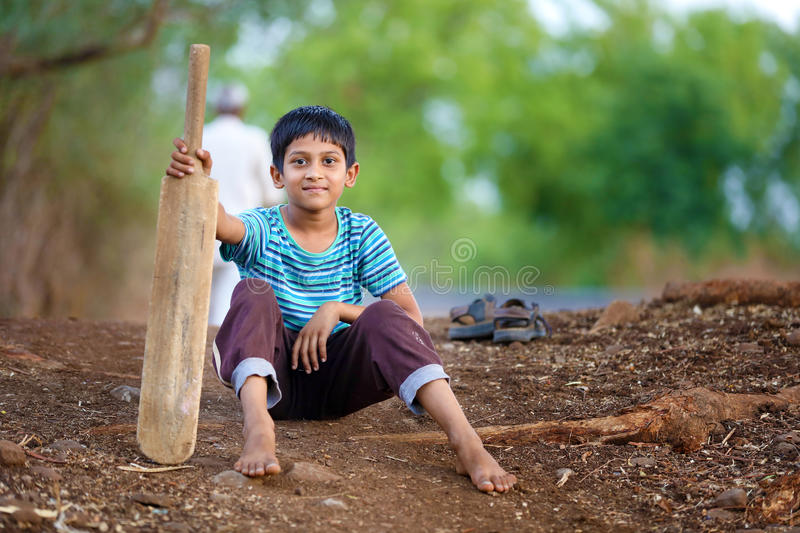 Rural Indian Child sitting on ground with bat. Playing Cricket stock images