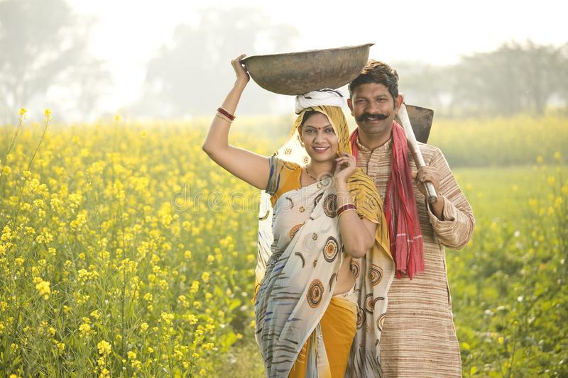 Rural couple with iron pan and hoe in agricultural field. Rural Indian couple with iron pan and hoe in rapeseed agricultural field royalty free stock image