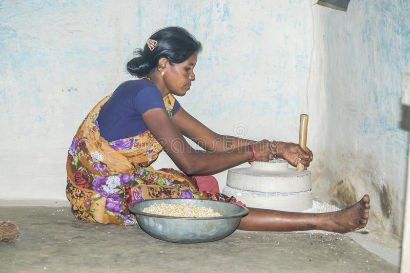 Rural Indian woman use hand mill to grind maize. stock photo