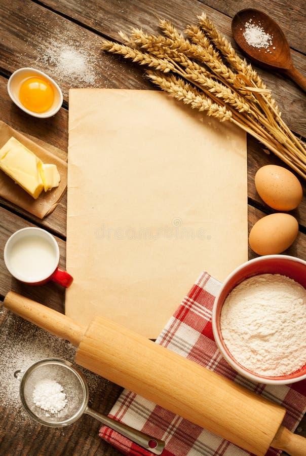 Rural kitchen baking cake ingredients and blank paper - background. Rural vintage wooden kitchen table with old blank sheet of paper, baking cake ingredients ( stock photos