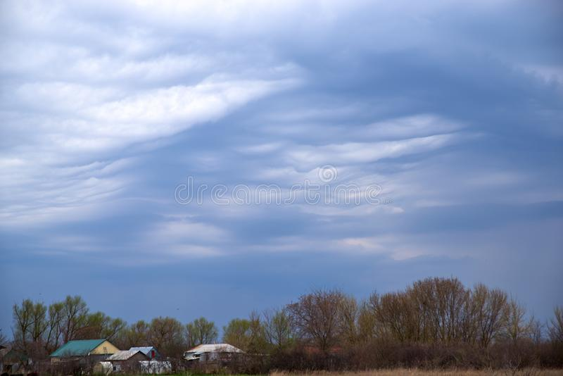 Rural landscape in dark colours with a dark ominous sky. Wavy low heavy clouds and sky.  royalty free stock photography
