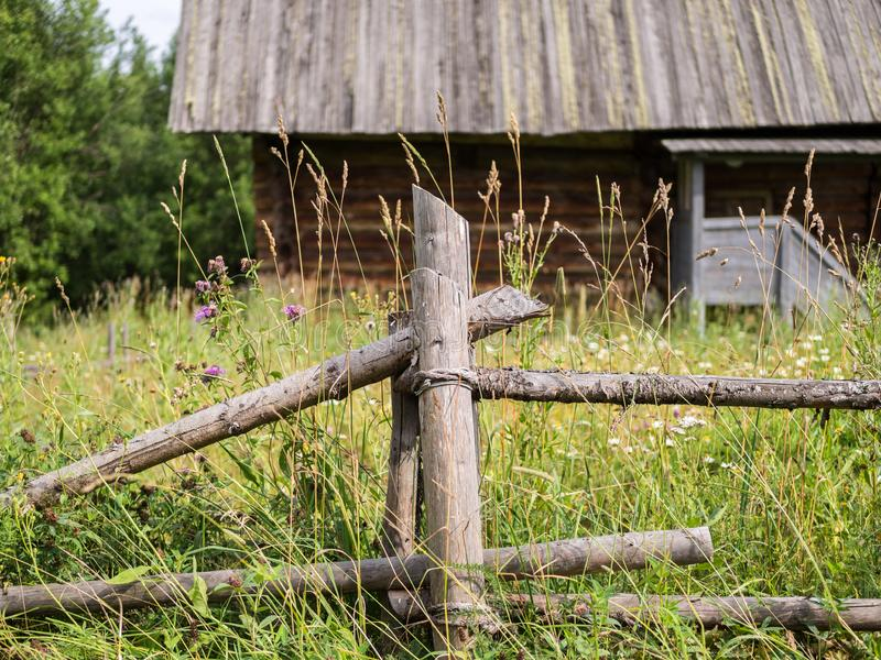 Country landscape with old rustic wooden fence and log house. Rural landscape with elements of wooden architecture stock images