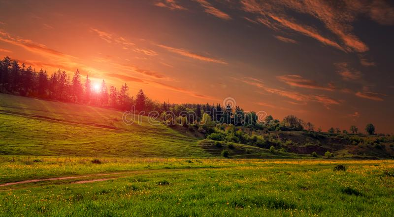 Rural landscape with a hill. Green meadow under sunset, colorful sky with clouds Dramatic morning scene. stock photography