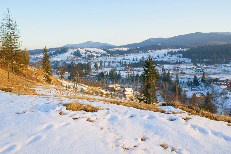 Rural landscape last snow in village in mountains in sunny evening royalty free stock images