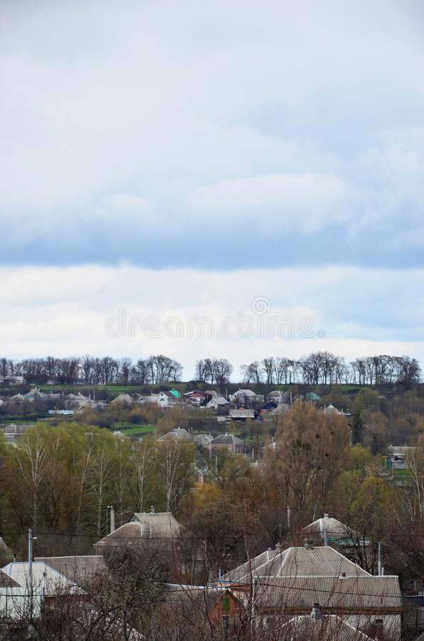 A rural landscape with many private houses and green trees. Suburban panorama on a cloudy afternoon. A place far from the cit. Y royalty free stock images