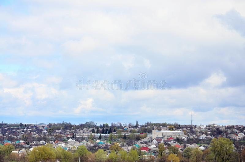 A rural landscape with many private houses and green trees. Suburban panorama on a cloudy afternoon. A place far from the cit. Y royalty free stock photo