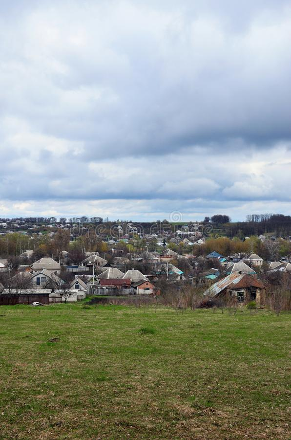 A rural landscape with many private houses and green trees. Suburban panorama on a cloudy afternoon. A place far from the cit. Y stock photos
