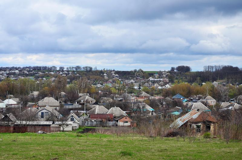 A rural landscape with many private houses and green trees. Suburban panorama on a cloudy afternoon. A place far from the cit. Y stock photo