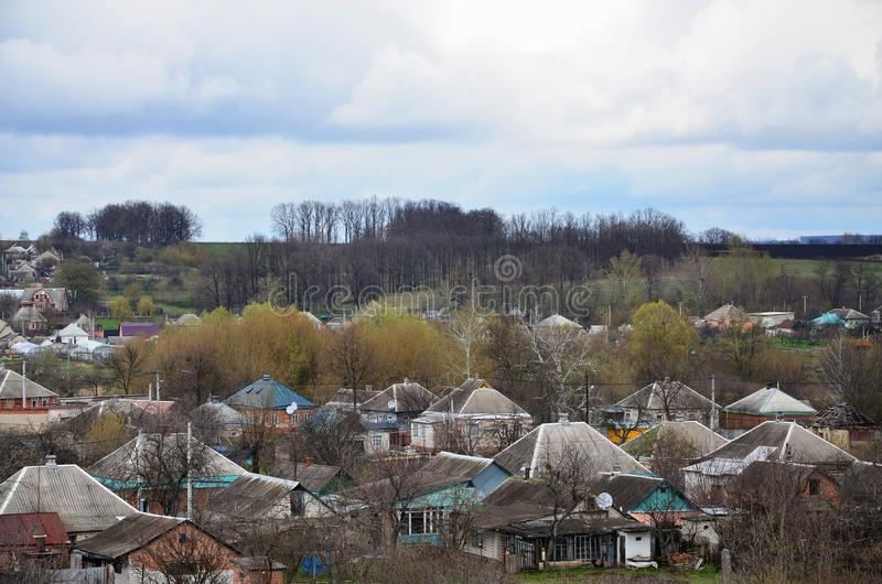 A rural landscape with many private houses and green trees. Suburban panorama on a cloudy afternoon. A place far from the cit. Y stock photography