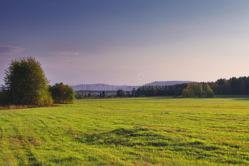 Rural landscape mown meadow against the background of the forest and mountains on the horizon. Early autumn. stock photography