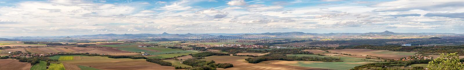 Rural landscape panorama with villages, fields and mountains in the background royalty free stock image
