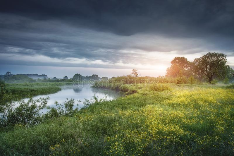 Rural landscape of river nature with cloudy sky at sunrise. Scenic nature in the morning. Green meadow near river. Bad weather in royalty free stock images