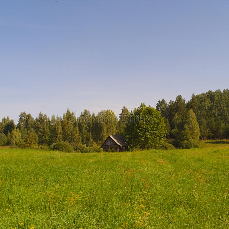 Rural landscape with a small wooden house. A rural landscape with a small wooden house or barn in the background royalty free stock photo