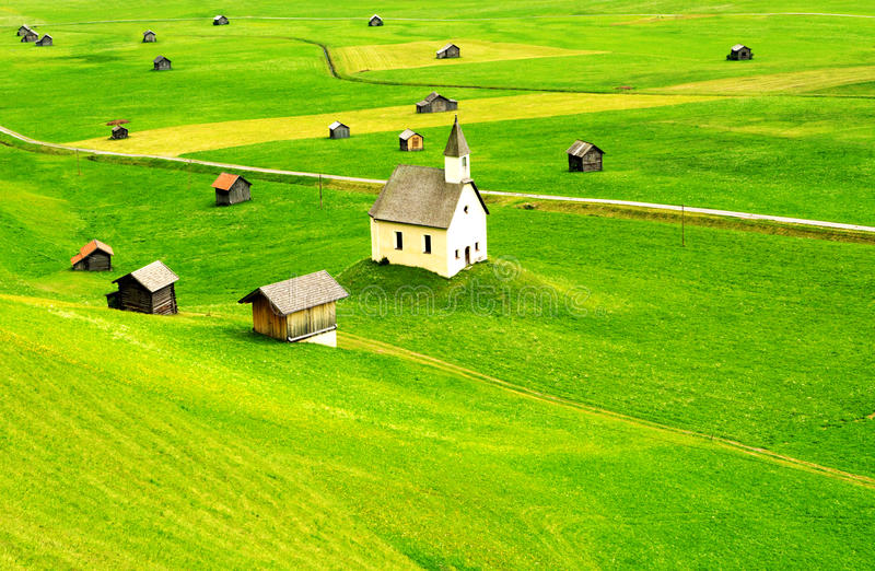 Tirol rural landscape. Karen Marie. Scenic view of green fields in landscape with scattered houses and old church, Tirol, Austria royalty free stock photos