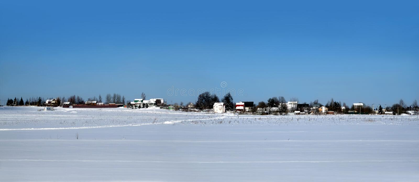 Rural landscape with a village on skyline after snow field under clear blue cloudless sky on bright sunny day panoramic view. Beautiful rural landscape with a stock photo