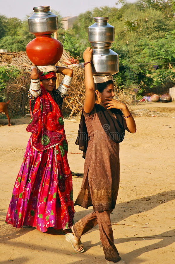 Rural Life in India. February 22, 2012-Gujarat,Bhuj,India,Asia-Women carrying water in a remote village of Gujarat royalty free stock image