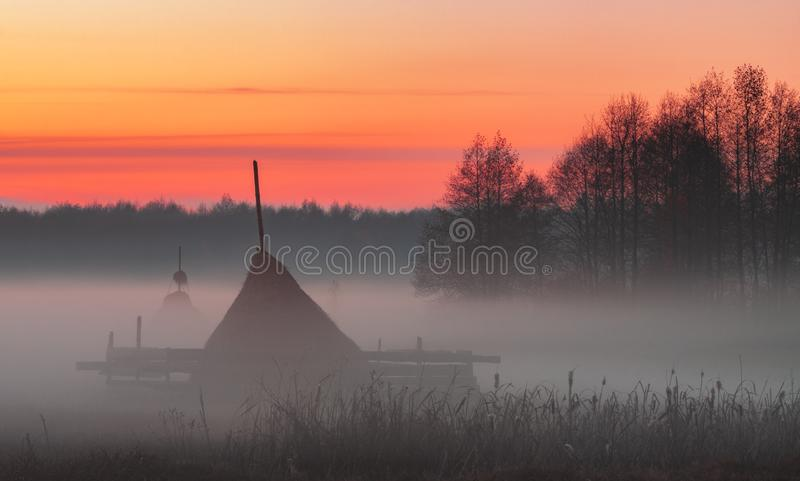 Rural meadow with haystacks in the foggy evening in red-orange light of the sunset sky. Landscape royalty free stock images