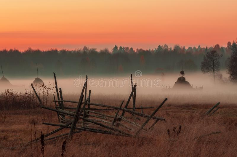 Rural meadow with haystacks in the foggy evening in red-orange light of the sunset sky. Landscape stock image