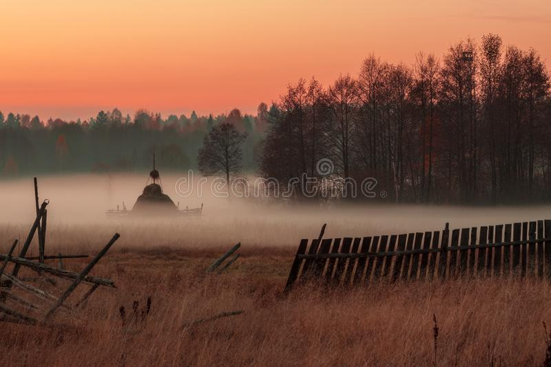 Rural meadow with haystacks in the foggy evening in red-orange light of the sunset sky. Landscape royalty free stock image