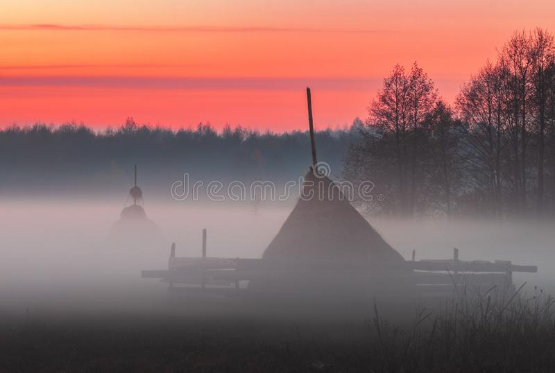 Rural meadow with haystacks in the foggy evening in red-orange light of the sunset sky. Landscape royalty free stock photo