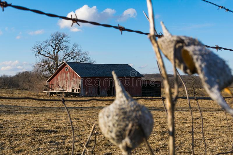Rural NW Illinois. Old wooden barn through the rusted barbed wire fence. Putnam County, Illinois, USA royalty free stock photos