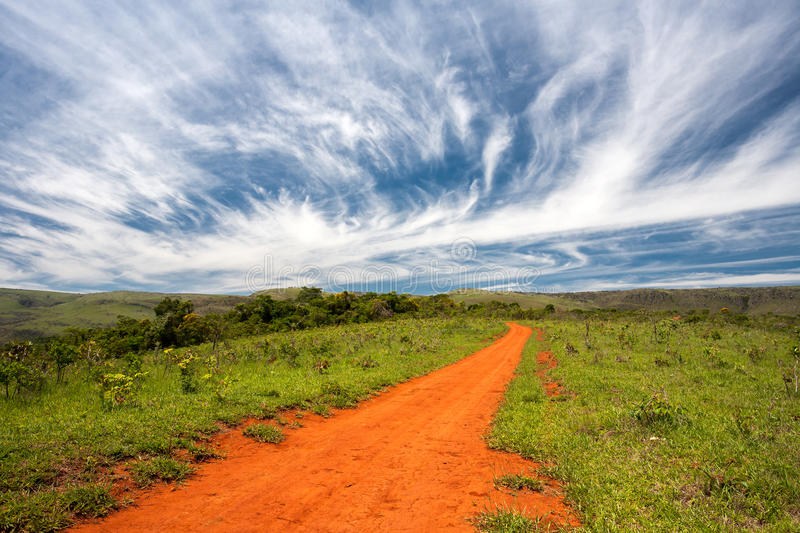 Rural orange dirt road. With blue sky and far horizon royalty free stock photo