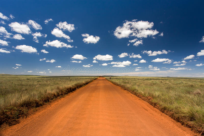Rural orange dirt road. With blue sky and far horizon royalty free stock photography