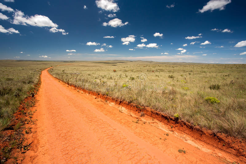 Rural orange dirt road. With blue sky and far horizon stock photos
