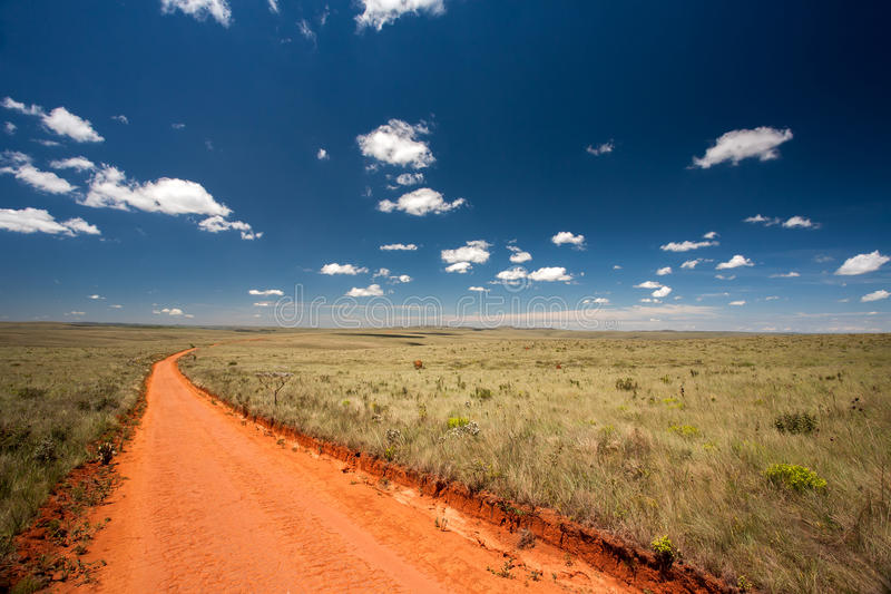 Rural orange dirt road. With blue sky and far horizon stock images