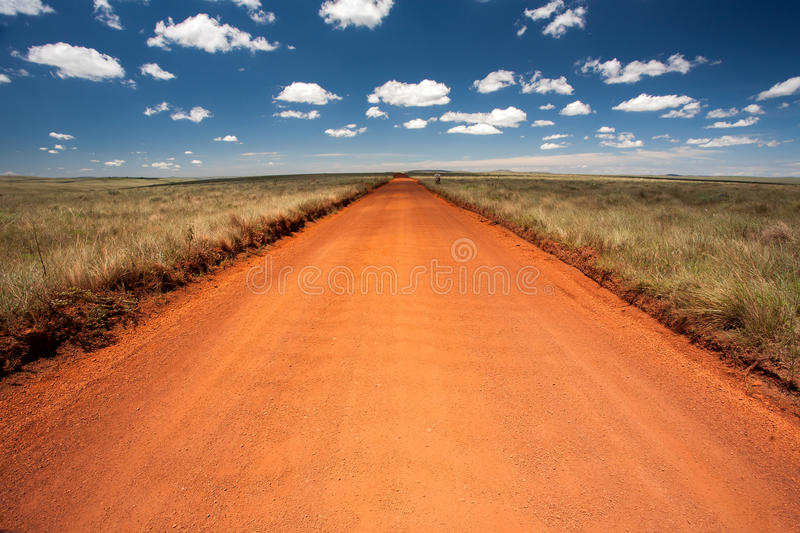 Rural orange dirt road with blue sky and far horizon. In MG - Brazil royalty free stock images