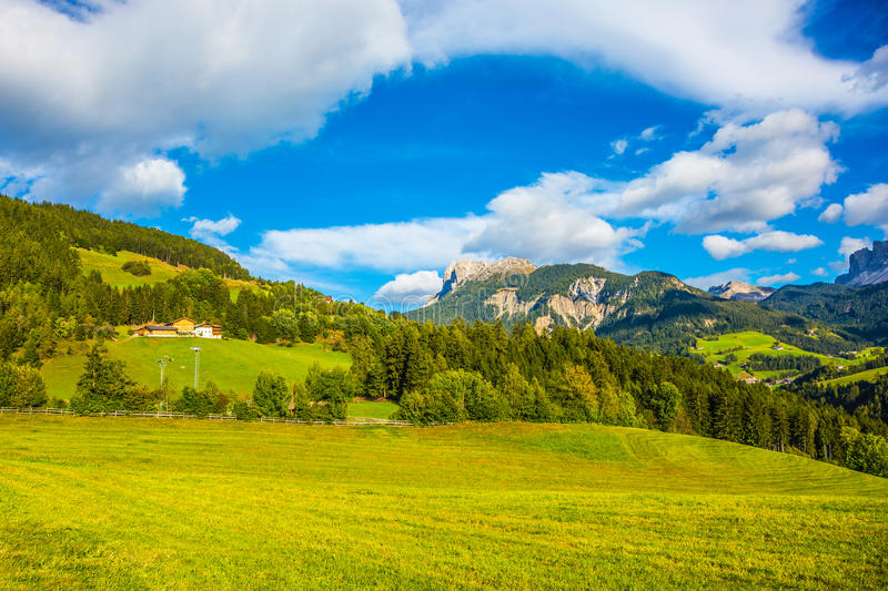 Rural pastoral. The concept of ecological tourism. Charming green grassy slope of the mountain. Rural pastoral in the Val de Funes, Dolomites. Warm autumn day stock image