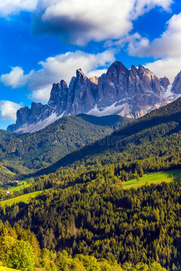 Rural pastoral in the Dolomites. Grassy slope of the mountain and wall of jagged rocks. Italy. Rural pastoral in the Val de Funes, Dolomites. The concept of stock image